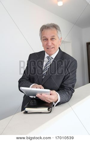 Senior man using electronic tab in building hall