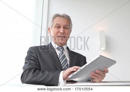 Senior businessman using electronic tab in building hall