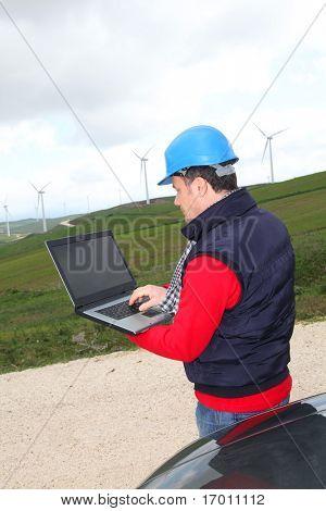 Engineer working on laptop computer in wind turbines field