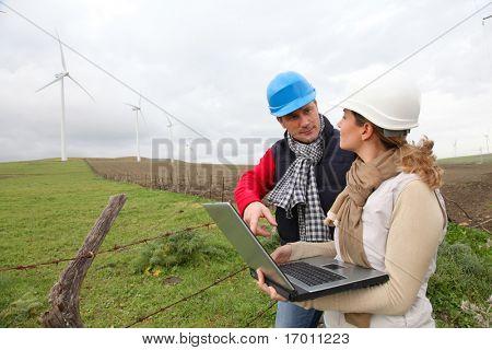 Engineers working by wind turbines field