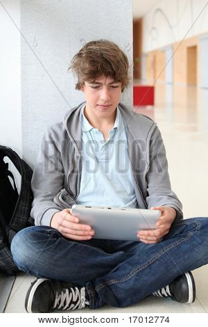School boy with electronic tablet sitting in hall