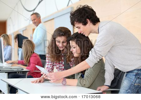 Group of teenagers in classroom with electronic tablet