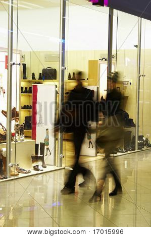 The man and the woman make purchases in shopping center.