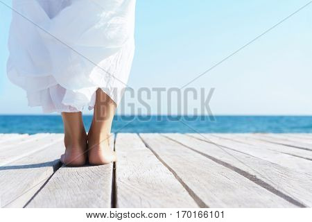 Legs of a woman in white dress on a wooden pier on summer.  Sea and sky background. Vacation, traveling and freedom concept.