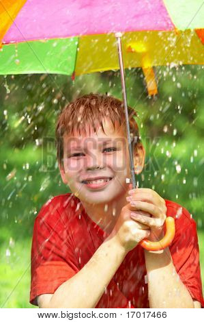 boy under an umbrella during a rain ...