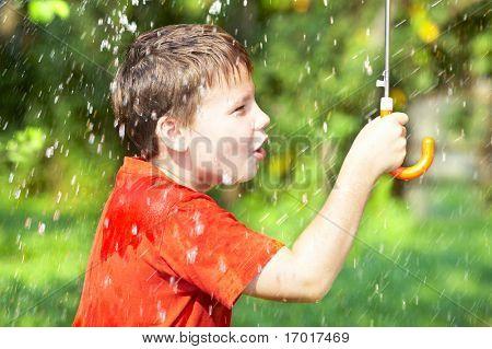 boy under an umbrella during a rain ...