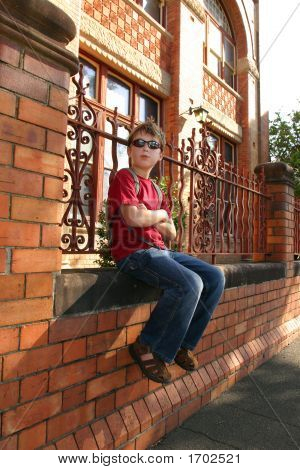 Child Sitting On Brick Wall
