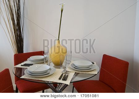 Glas dining table set up with red chairs, yellow vase, plates and cutlery
