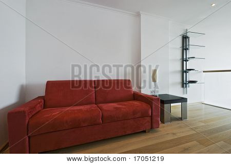large chunky sofa in red with a small side table and shelves