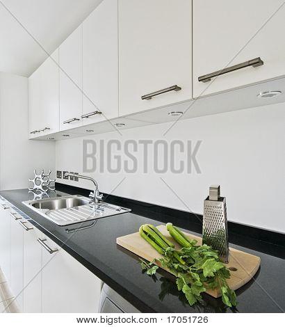 cocina contemporánea blanco con encimera de granito negro