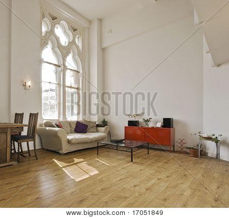 Apartamento de tecto alto, com grandes janelas góticas