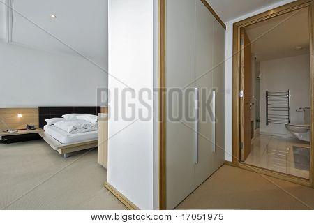 modern bedroom with a walk in wardrobe and en-suite bathroom