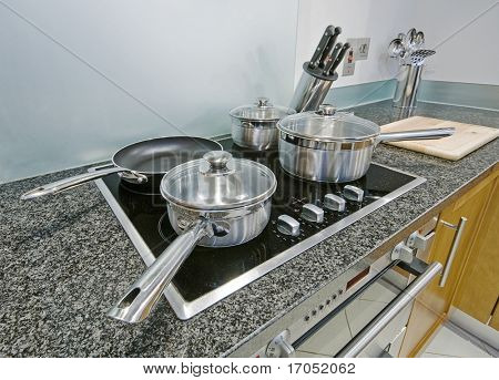kitchen detail with induction electric hob and cooking pans