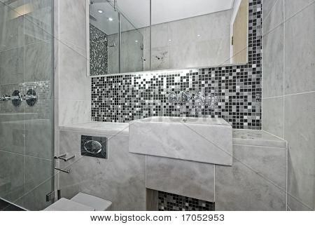 modern en-suite bathroom with marble sink and mosaic tiles