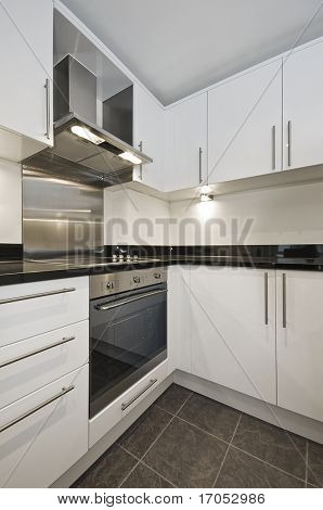 modern luxury kitchen in white with black granite worktop