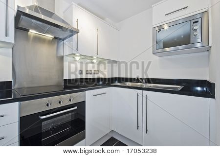 modern white kitchen unit with built-in electric appliances