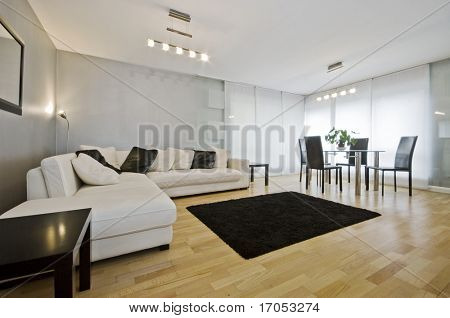 modern luxury living room with white leather corner sofa and round dining table