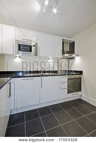modern contemporary kitchen in white with black stone worktop