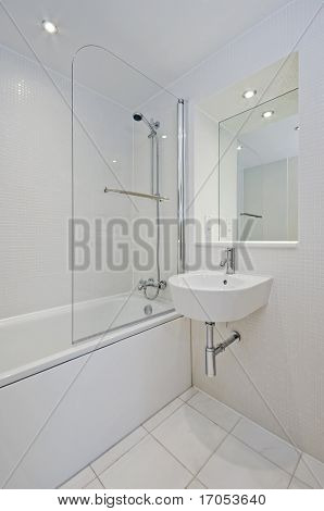 white bathroom with ceramic suite and mosaic tiles