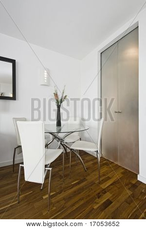 dining area with a glass top round table and four seats
