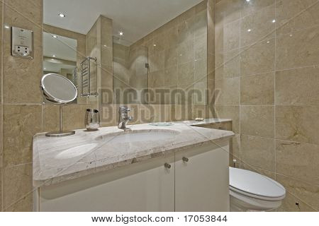luxury modern bathroom with marble tiles and white ceramic suite