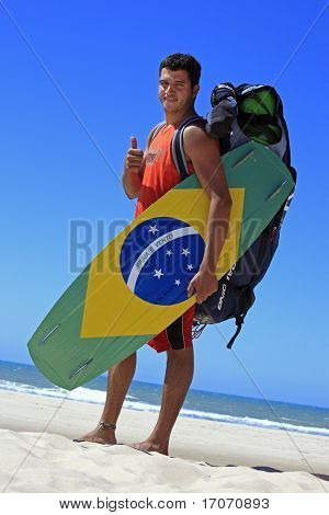 Kitesurfer with the brazilian painted on the board in prainha beach near fortaleza