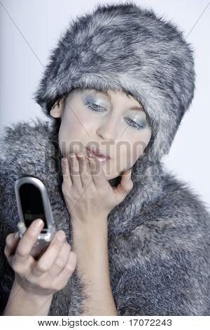 studio shot portrait of a beautiful woman russian type in a fur coat and hat kissing and saying hello by cellphone