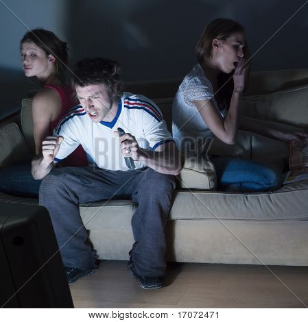 pictures in a living room of two young girls and a man sitting on a couch  watching on tv  sport event