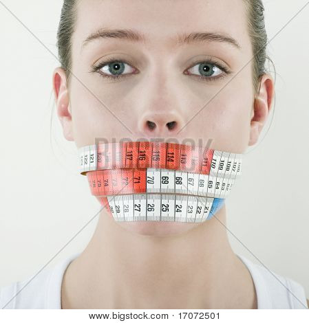 studio portrait on isolated background of a young beautiful caucasian woman by a meter ribbon