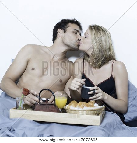 beautiful young caucasian couple in a bed on isolated background having breakfast in bed