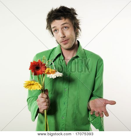 studio shot pictures on isolated background of a funny man offering fake flowers