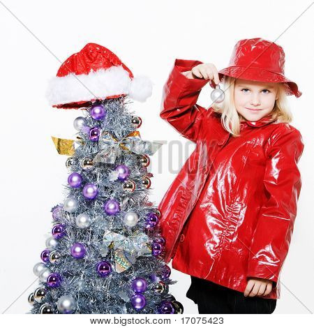 indoors picture of a little girl preparing christmas tree on isolated white background