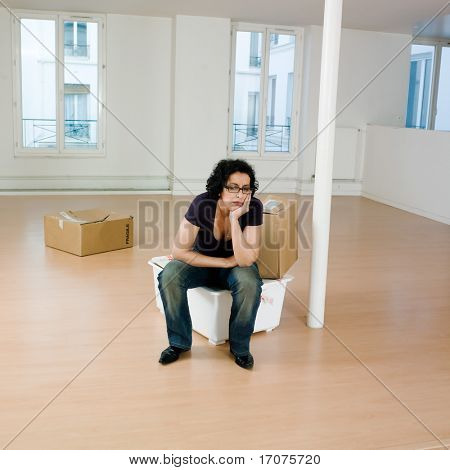 man sitting on the floor inside an empty loft apartement with tax forms and laptop computer