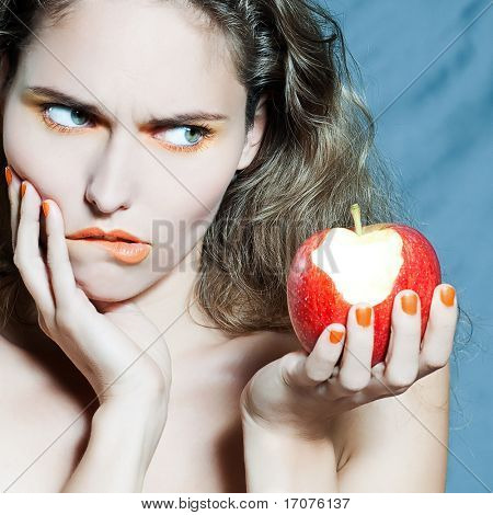studio portrait of a beautiful woman holding apple frui