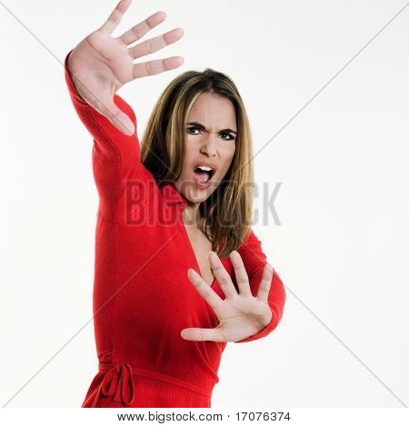 beautiful brunette caucasian woman on white background shielding with her arms
