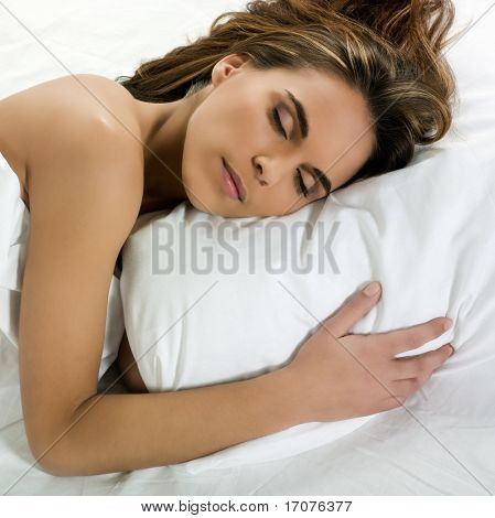 beautiful caucasian woman sleeping on a white bed