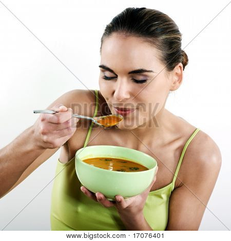 beautiful brunette caucasian woman on white background eating soup