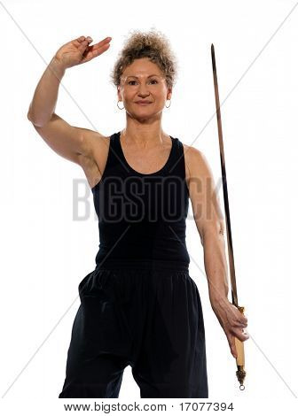 mature woman praticing tai chi chuan with sword in studio on isolated white background