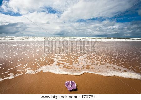 flip flop in front of the sea of sitio do conde in bahia state brazil
