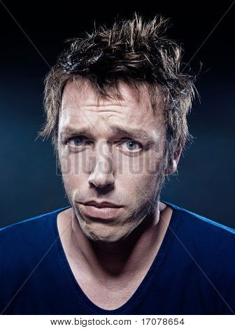 studio portrait on black background of a funny expressive caucasian man puckering sad