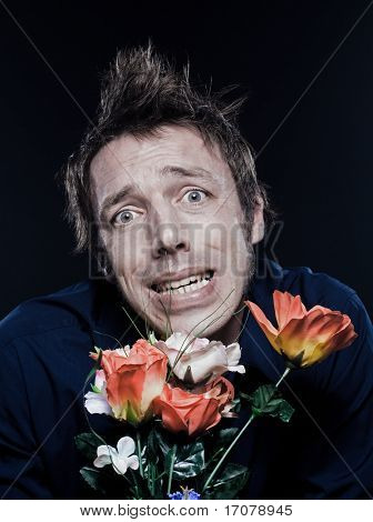 studio portrait on black background of a funny expressive caucasian man offering flowers stresse