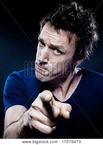 studio portrait on black background of a funny expressive caucasian man pointing menace suspicious
