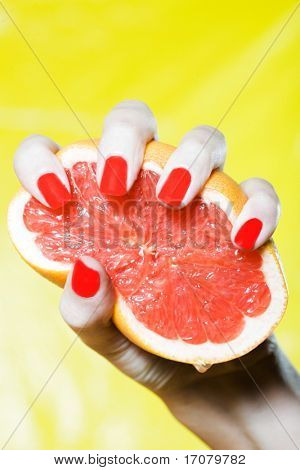 woman hand with red nails and colorful background squeezing grapefruit