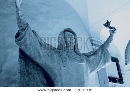 A statue of Saint Catherine in a church in Siena, Italy. The shot has been toned in blue to give a duotone effect.