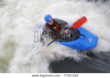 A motion blurred shot of a kayaker in whitewater