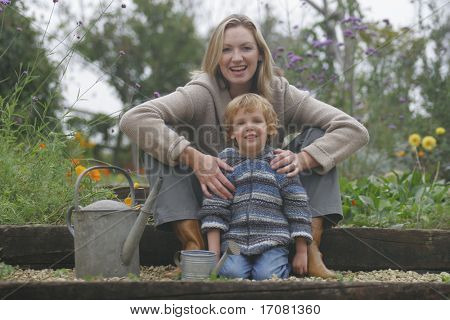 A young mother and her son in a flower filled garden with their watering cans