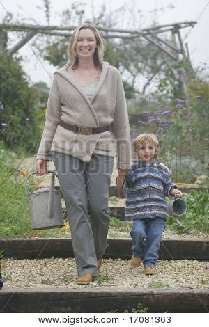 A young mother and her son walking through a flower filled garden with watering cans