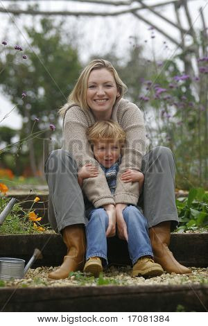 A mother and her young son cuddle up in a flower filled garden.
