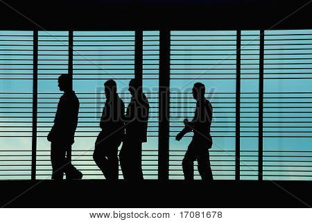 Silhouettes of workers/executives in front of a hi tech background