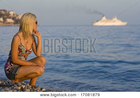 A beautiful young woman on a beach bathed in sunshine watching a cruise ship on the horizon